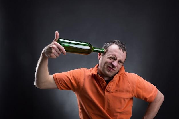Мужчина сует ему в голову бутылку вина