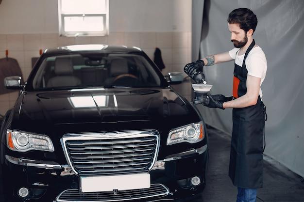 Man polish a car in a garage