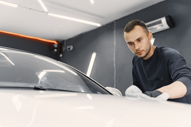 Man polish a car in a garage