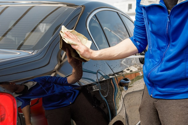 Man polishes the car, uses a microfiber cloth and polish to wipe the car's body with polish.
