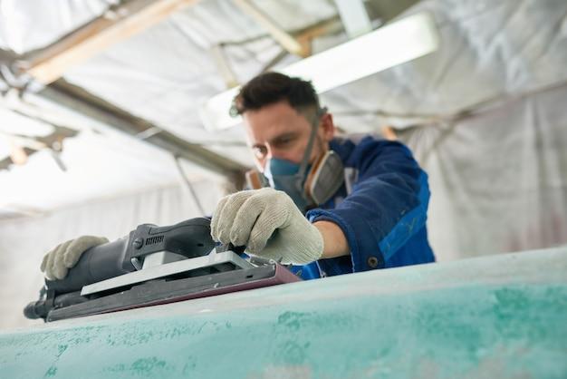 Человек полировки лодки в мастерской