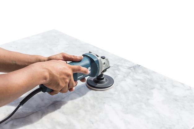Человек, полирующий мраморный каменный стол маленькой угловой шлифовальной машиной