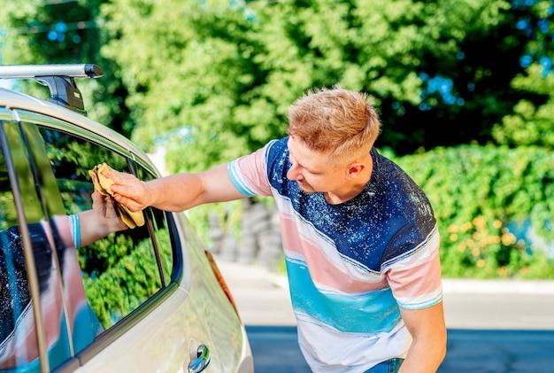 輝く車の窓を布で磨く男