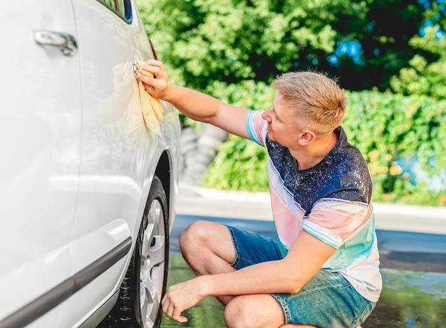 Man polishing white car with rug outdoors