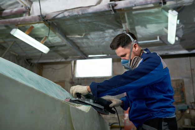 Человек полировки яхт в мастерской