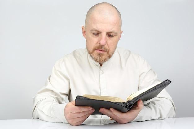 남자가 성서 책을 읽고 숙고하다