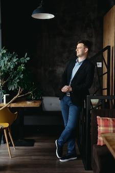 ロフトのモダンなスペースでポーズをとる男の肖像画
