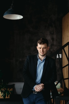 Ritratto dell'uomo che posa in uno spazio moderno del sottotetto