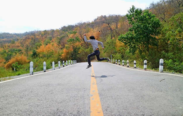 Man in the pose of jumping across the mountain road among color changing forest