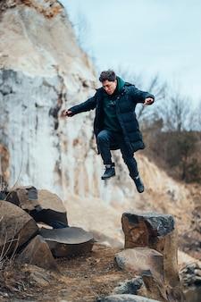 男は採石場でポーズとジャンプ