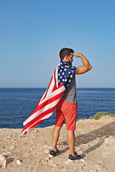 Man poses in form of hero and american flag as cloak outdoor. independence day of united states of america. concept of american patriotic people