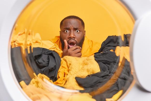 L'uomo posa dall'interno della lavatrice mette il bucato nella lavatrice ha un'espressione sbalordita la pelle scura fa i lavori di casa lava i vestiti a casa
