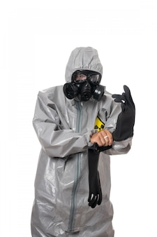 A man poses in a gray protective suit, with a gas mask, posing while standing