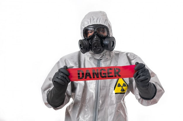 A man poses in a gray protective suit with a hood on his head, with a protective gas mask, posing while standing on a white background, holding a red hazard tape in his hands. danger tape. protection.