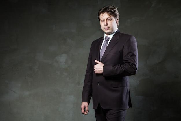 남자는 그런 지 회색 벽 앞에서 양복을 입고 포즈를 취합니다. 프리미엄 사진