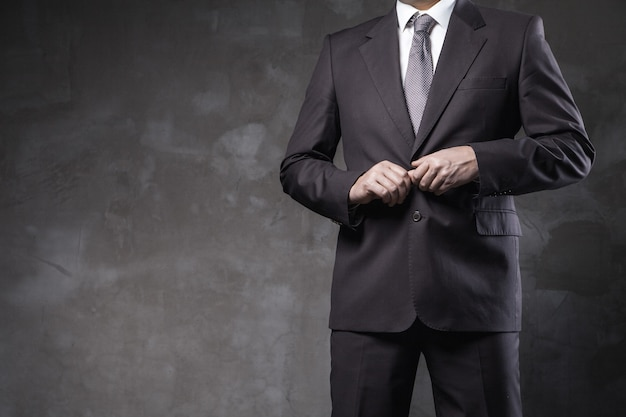 남자는 그런 지 회색 벽 앞에서 양복을 입고 포즈를 취합니다.