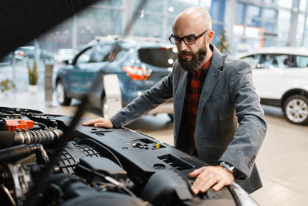 Man poses at new pickup truck with opened hood, car dealership. customer in vehicle showroom, male person buying transport, auto dealer business
