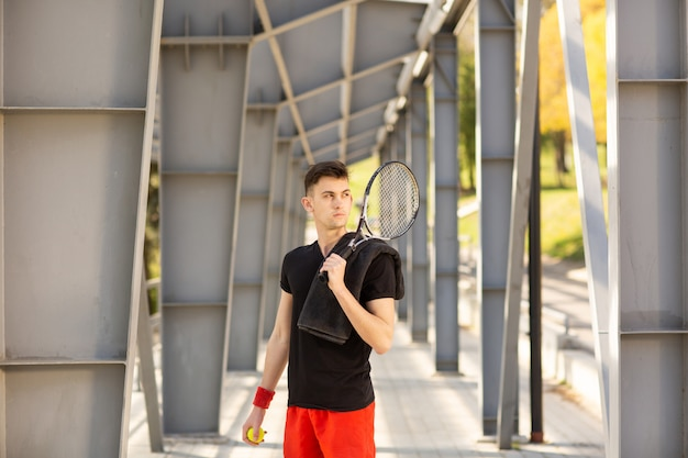 The man poses outdoors with a tennis racket and a ball. a towel is hanging on his shoulder.