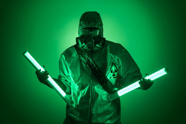 A man poses in a protective suit with a hood on his head, with a protective gas mask, posing while standing against a green background, holding uranium lamps in her divorced hands. danger
