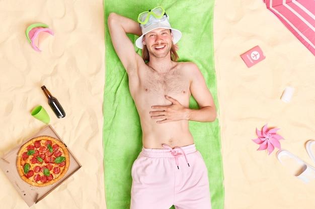 男は緑のタオルの上に上半身裸でポーズをとる日よけ帽をかぶって、ショートパンツは夏休みを楽しんでいますビールと一緒においしいおやつを食べて夏休みを楽しんでいます
