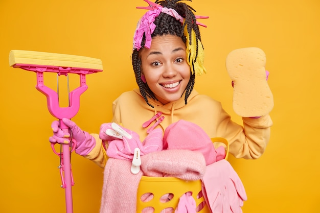 Man poses with mop and sponge brings house in order does laundry wears protective rubber gloves isolated on yellow wall
