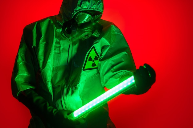 A man poses in a yellow protective suit with a hood on his head, with a protective gas mask, posing while standing against a red background, holding a green light uranium lamp in his hands.