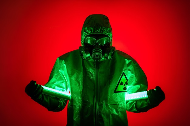 A man poses in a yellow protective suit with a hood on his head, with a protective gas mask, posing while standing against a red background, holding uranium lamps in his hands. diode lamps.