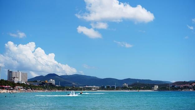 Человек позирует на новом флайборде на пляже далеко - летнее время