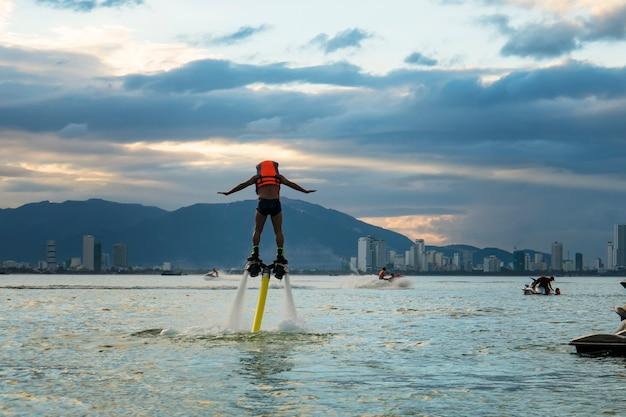 해질녘 열 대 해변에서 새로운 플라이보드에서 포즈를 취하는 남자. 긍정적인 인간의 감정, 감정, 기쁨. 재미있는 귀여운 남자들이 휴가를 보내고 여름을 즐기고 있습니다.