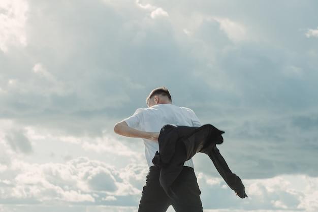 曇り空の前でカメラにポーズをとって男。