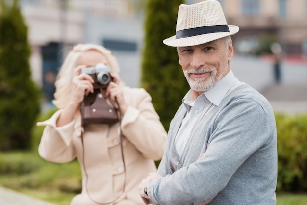 Man posing in hat. woman take pictures on camera.