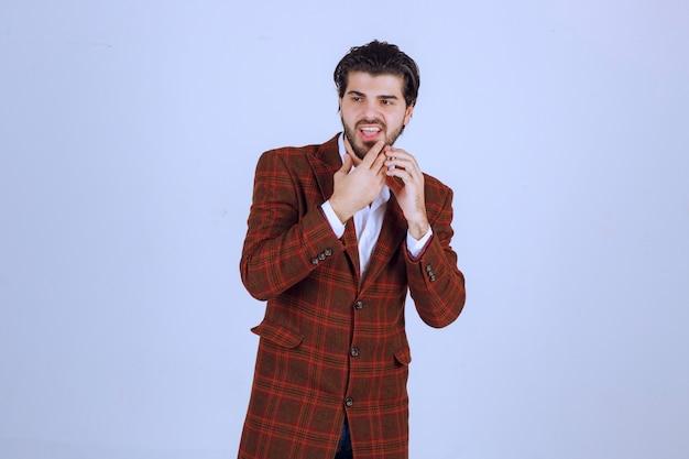 トレンディな茶色のチェックブレザーでポーズをとる男
