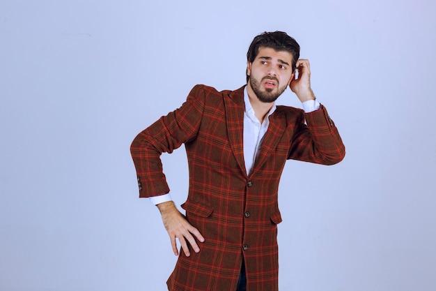 トレンディな茶色のチェックブレザーでポーズをとる男 無料写真