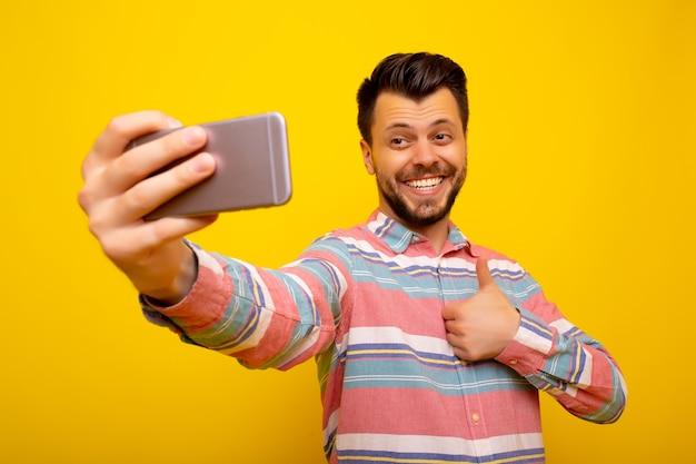 黄色の背景の上に孤立してポーズをとる男は携帯電話で自分撮りを取ります