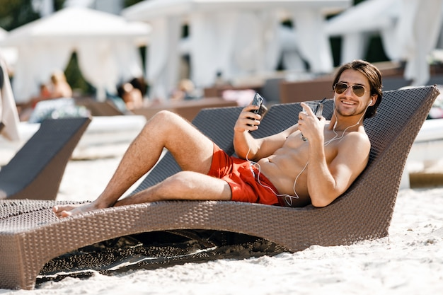 A man posing and listening to music on the beach
