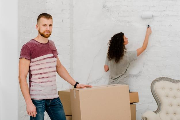 Uomo che posa vicino alla parete della pittura della donna