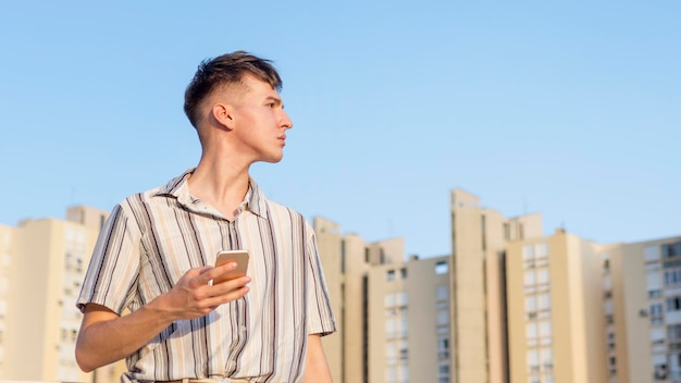 Man posing outdoors while holding smartphone