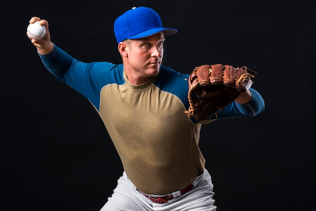Man posing with baseball glove and ball