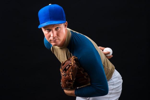 Man posing with baseball glove and ball