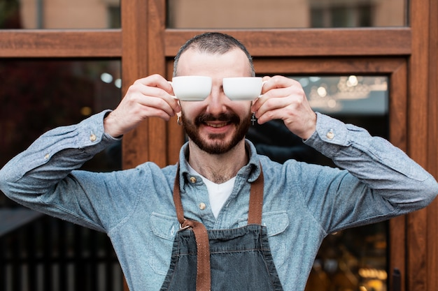 Man posing with coffee cups