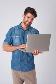 デニムシャツとラップトップでポーズをとる男