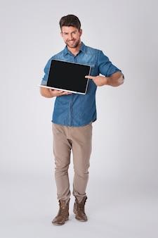 Uomo in posa con camicia di jeans e laptop