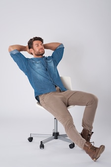 Мужчина позирует в джинсовой рубашке, сидя на стуле