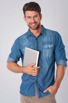 Uomo in posa con camicia di jeans e tablet
