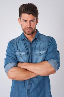 Uomo in posa con la camicia di jeans