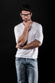 Uomo in posa con occhiali da vista, jeans e t-shirt bianca