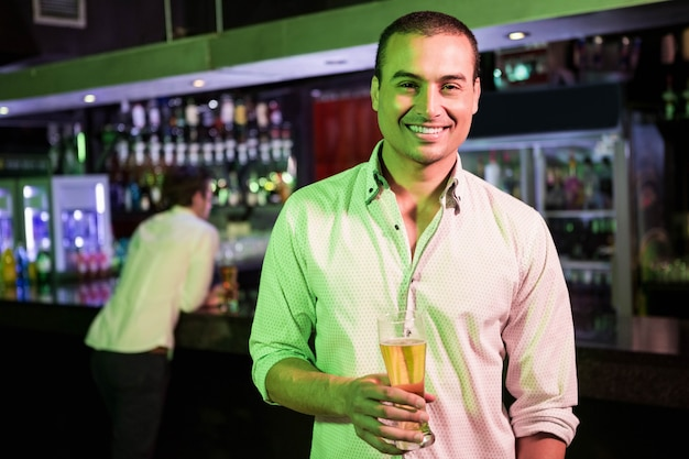Man posing with glass of beer and friend at bar