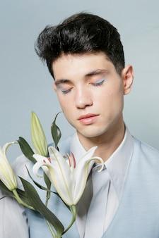 Мужчина позирует с лилией и закрытыми глазами