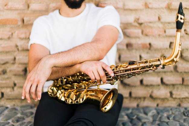 Man posing with saxophone in street