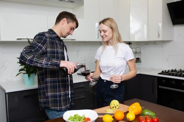 男は台所で彼の幸せな女性のためにグラスワインを注ぐ